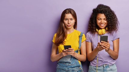 Dissatisfied young woman has no internet connection on mobile phone, cheerful African American girl has amusing chat in network, listens music in headphones isolated on purple wall. Technology concept