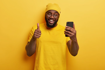 I like your idea. Black smiling guy makes video call via cell phone, keeps thumb raised, agrees with something, uses modern technologies, stands against yellow wall. Monochrome shot. Body language
