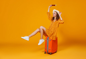 concept of travel. happy woman girl with suitcase and  passport on  yellow background. Wall mural
