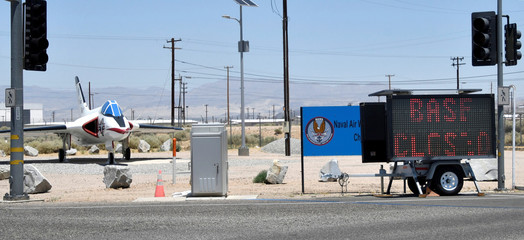 """A sign reading """"Base Closed"""" is parked outside the entrance to China Lake Naval Air Weapons Station after an earthquake near Ridgecrest"""