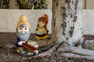 A pair of yard gnomes working in the garden by a tree
