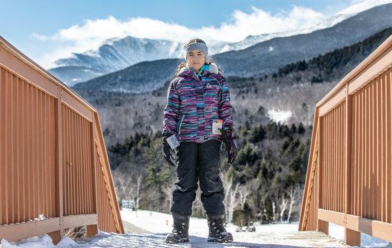 Girl in winter gear with snowy mountain backdrop