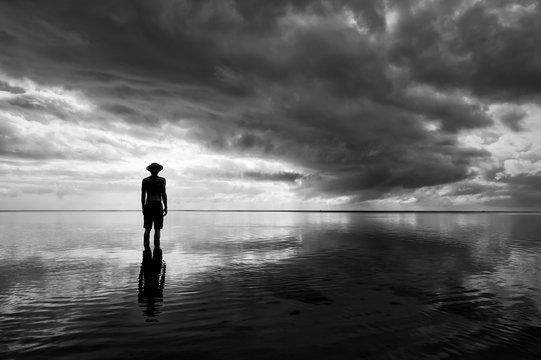 Moody monochrome silhouette of man in hat standing in calm shallow waters reflecting dramatic skyscape on the sea horizon
