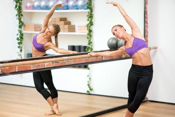 Woman exercising side barre stretch at gym