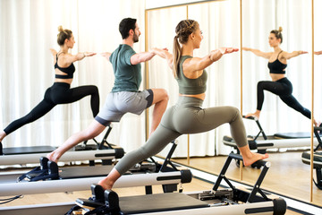 Class in a gym doing pilates standing lunges Fototapete