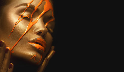 Orange paint smudges drips on woman face. Liquid drops on beautiful model girl's mouth, gold metallic skin makeup