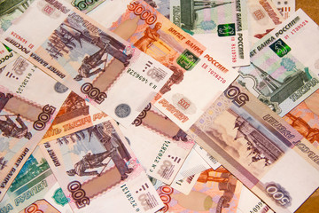 Banknotes of the Russian currency of different denominations scattered on the table - a sign of wealth and prosperity.