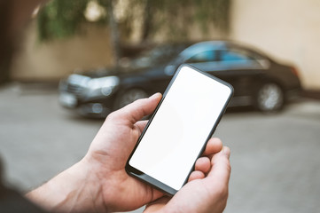 Mock Up Smartphone in man's hand, in the background a black car.