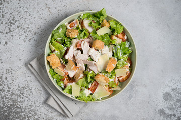 Caesar salad with chicken, Parmesan and wheat croutons on a vintage grey background. Light diet dinner.