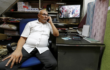 M. J. M. Faizal, 55, owner of Expo Leather talks on the phone next to a screen of security cameras, at his shop during an interview with Reuters in Kandy