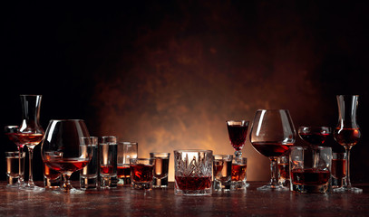 Poster de jardin Alcool Set of strong alcoholic beverages in glasses on a brown background.