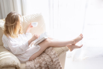 Woman sitting in white armchair, reading the book and and drinking coffee at the morning in bedroom. Relaxing and good morning concept. Fotomurais