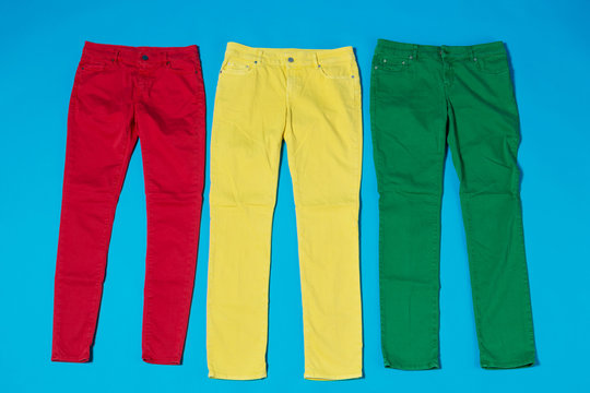 three colored pants on a blue background, the concept of a joyful life and shopping