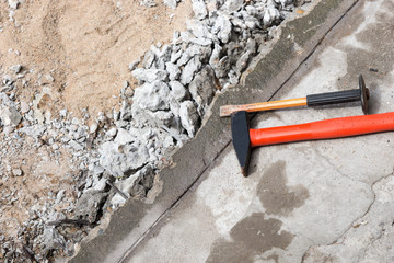 Hammer and chisel on the concrete slab