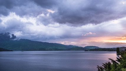 Sunset over the lake and the tops of the mountains. Overcast