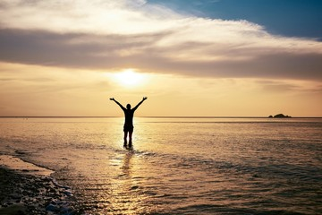 Happy man with arms outstretched standing in sea