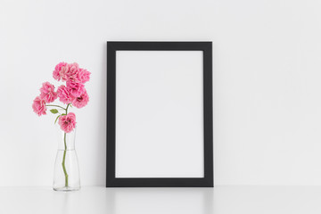 Black frame mockup with pink roses in a glass vase on a white table.Portrait orientation.