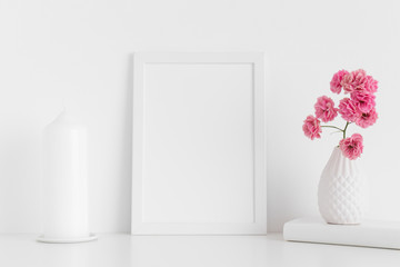 White frame mockup with pink roses in a vase and candle on a white table.Portrait orientation.