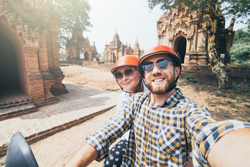 Young Caucasian couple making selfie on a scooter while driving through temples and pagodas of ancient Bagan in Myanmar