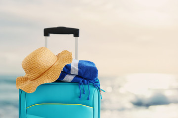 Fototapete - holidays. travel concept. blue suitcase with female hat and beach towel infront of tropical background