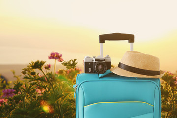 Wall Mural - recreation image of traveler luggage, camera and fedora hat infront of a rural lanscape. holiday and vacation concept