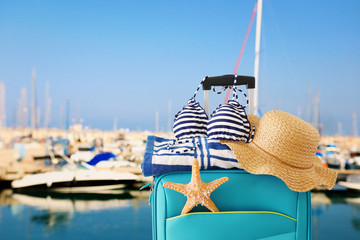 Wall Mural - holidays. travel concept. blue suitcase with female hat, starfish, bikini and beach towel in front of marina with yachts background