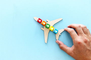 Transportation concept image, man's hand holding toy airplane with people icons over blue background. Travel and leadership idea