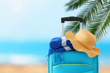 Wall Mural - holidays. travel concept. blue suitcase with female hat and beach towel infront of tropical background