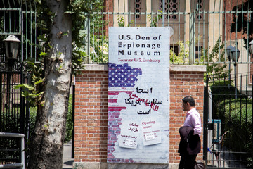 A man walks in front of a banner with anti-U.S. messages in Tehran