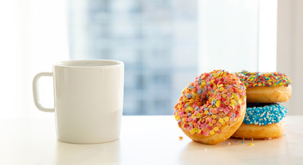 Doughnuts and coffee cup on white color table. Closeup view