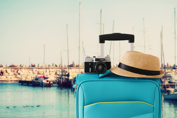 Wall Mural - recreation image of traveler luggage, camera and fedora hat infront of marina with yachts background. holiday and vacation concept