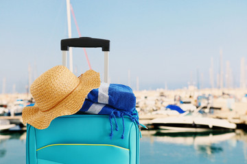 Wall Mural - holidays. travel concept. blue suitcase with female hat and beach towel infront of marina background
