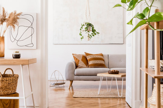 The stylish boho interior of living room at nice apartment with gray sofa, wooden desk, bamboo shelf, coffee table, honey yellow pillows, plants and elegant accessories. Mock up paintings on the wall