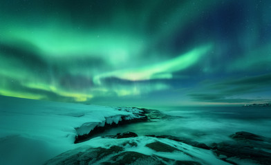 Tuinposter Noorderlicht Aurora borealis over ocean. Northern lights in Teriberka, Russia. Starry sky with polar lights and clouds. Night winter landscape with aurora, sea with stones in blurred water, snowy mountains. Travel