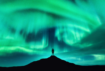 Poster Green coral Aurora borealis and silhouette of a man on the mountain peak. Lofoten islands, Norway. Beautiful aurora and man. Alone traveler. Sky with stars and polar lights. Night landscape with northern lights