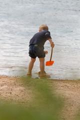 Chłopiec bawiący się łopatką w morzu