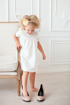 Little pretty girl in white dress trying on mummy's shoes