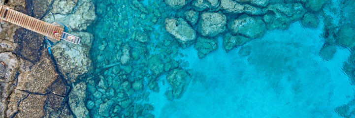 Foto op Plexiglas Cyprus An aerial view of the beautiful Mediterranean Sea, with a wooden pier and a rocky shore, where you can see the textured underwater corals and the clean turquoise water of Protaras, Cyprus