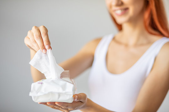 Wet wipes: women take one wipe from package for cleaning