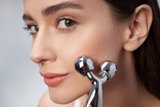 Attractive young woman with perfect skin using platinum facial massager