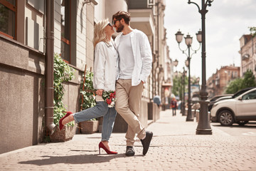 Romantic couple is standing and smiling outdoors