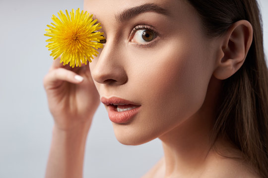 Beautiful young woman posing with yellow flower