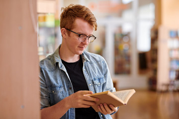 Casual student in eyeglasses reading book in college library