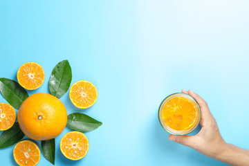 Hand of woman holding glass of orange juice and orange fruits with sliced pieces and leaves on blue background, flat design