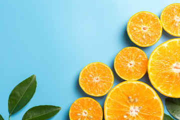 Sliced orange fruits with leaves on blue background, flat design Wall mural