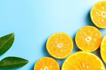 Sliced orange fruits with leaves on blue background, flat design
