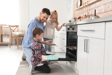 Father with his kids baking cookies in oven at home