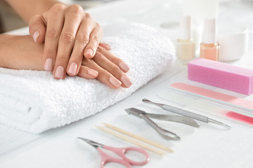 Woman waiting for manicure and tools on table, closeup with space for text. Spa treatment