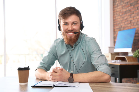 Young man with headset looking at camera and using video chat in home office