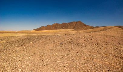 wasteland desert scenery landscape photography of sand stone dry valley foreground and mountains background in warm sunny weather time